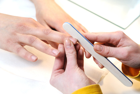 Manicure in a beauty salon. Manikyurist filing nails on female fingers. Stock Photo