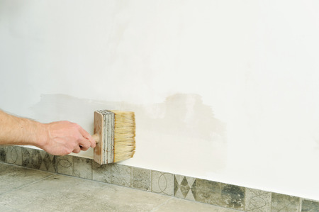 Worker adhesive wallpapers. The hand of man holding a brush and put glue on the wall. Stock Photo