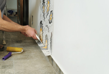 Worker adhesive wallpapers. He presses for better wallpaper adhesive using a roller and scraper. Stock Photo