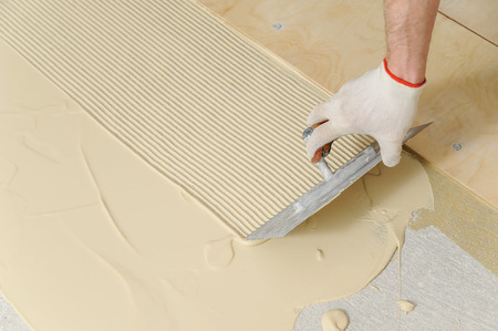 Laying plywood on the floor. A worker puts glue for gluing of the plywood Stock Photo