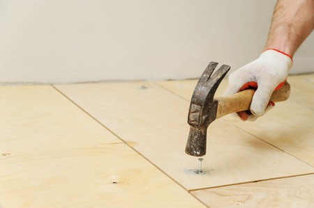 Laying plywood on the floor. Worker inserts the dowel to fix a plywood.