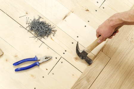 Laying hardwood parquet. Worker fixes the boards one by one. Stock Photo