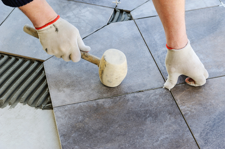 Laying Ceramic Tiles. Worker putting tiles on the balcony. Stock Photo