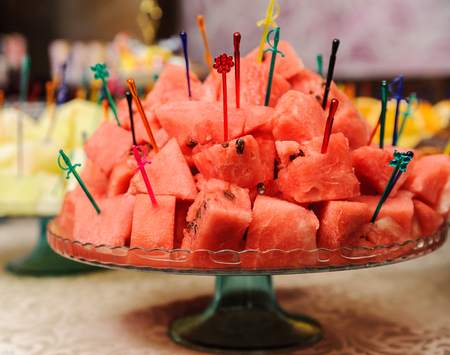 Slices of watermelon is punctured skewers on a tray