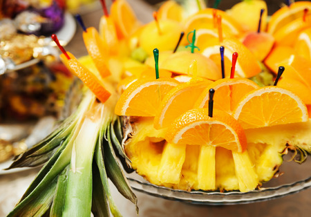 Slices of orange is punctured skewers on a tray