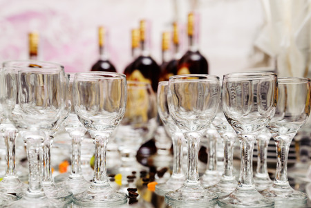 Glasses on mirror surface against the backdrop of bottles of brandy
