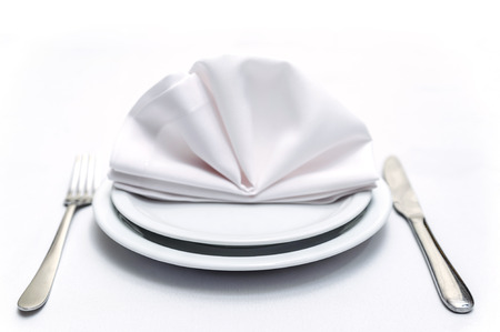 Place settings with two plates, one on one, napkin over them, knife and fork Stock Photo
