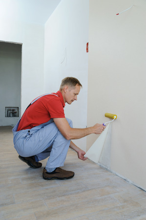 Worker pasting wallpapers. He presses for better adhesion using roller. Stock Photo