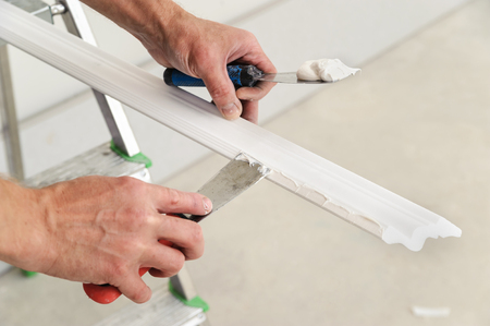 Installation of ceiling moldings. Worker puts glue on plastic molding for further fixing it to the ceiling Stock Photo