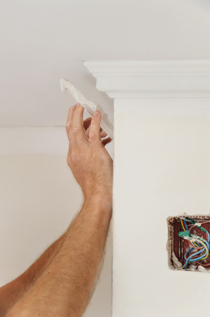 Installation of ceiling moldings. Worker fixes the plastic molding to the ceiling Stock Photo