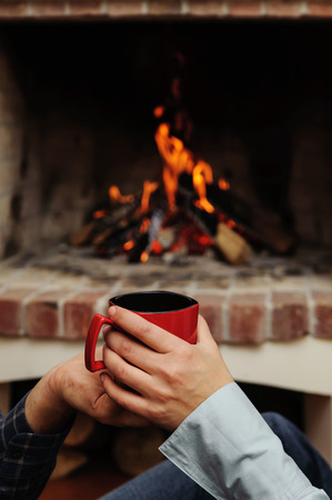 Red cup in the hands of man and woman on the background of fire