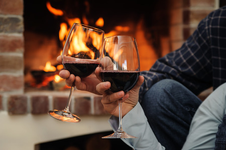 Two glasses of wine in the hands of man and woman on the background of fire