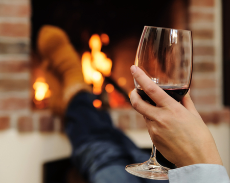 Glass of wine in hand woman on the background of fire Stock Photo