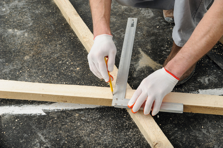 measures: Worker measures off a wooden beam to cut it further.