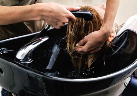 Hairstylist washing woman hair. Hairdressing beauty salon