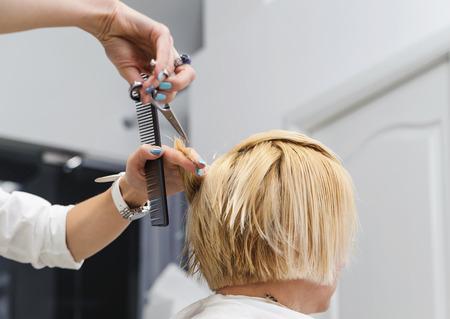 Hairdresser cutting blonde hair with scissors