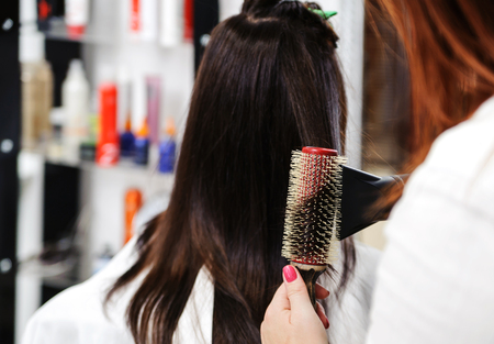 Hairdresser creates  hairstyle  using the brush and hair dryer