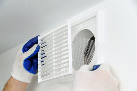 Worker installs ventilation grille on the wall. Stock Photo