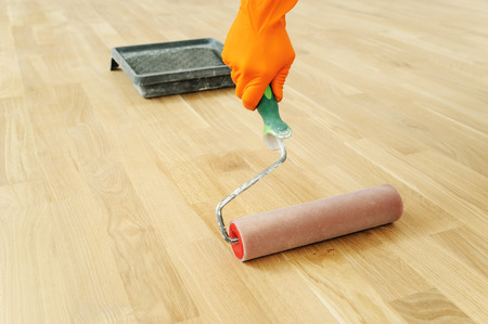 Lakken houten vloeren. Gebruik de roller voor het coaten van vloeren. Stockfoto