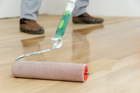 parquet floor layer: Lacquering wood floors. Use roller for coating floors. Stock Photo