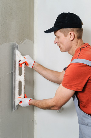 The worker puts f inishing layer of stucco on the wall using a plastering trowel