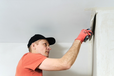 plasterer: The worker puts f inishing layer of stucco on the wall using a spatula