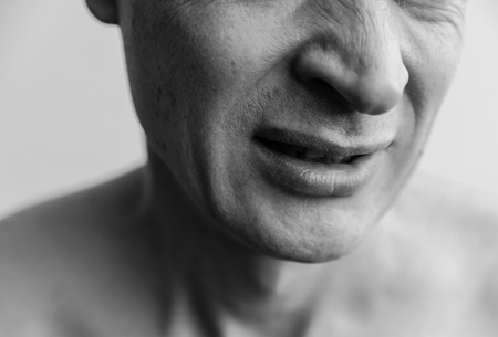abomination: Mimicry showing  not like. The lower part of the face of a man closeup. Black and white images