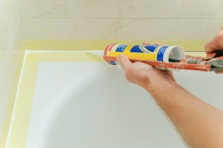 caulk: Worker puts silicone sealant to caulk the joint between tub and wall.