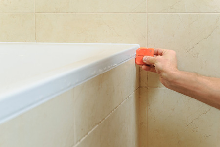 hermetic: Worker puts silicone sealant to caulk the joint between tub and wall.