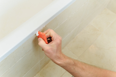 smoothing: Worker smoothing silicone sealant between the bath and the wall using a spatula. Stock Photo