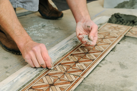 Worker Putting Tiles On The Floor He Places Plastic Crosses Stock