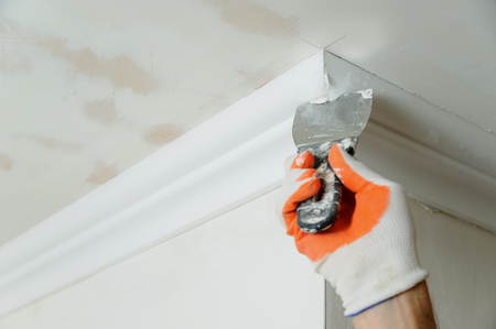 Installation of ceiling moldings. Worker puts glue on plastic molding for fixing it to the ceiling. Stock Photo