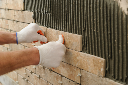 Installing the tiles on the wall. A worker putting tiles in the form of brick. Фото со стока - 66208998