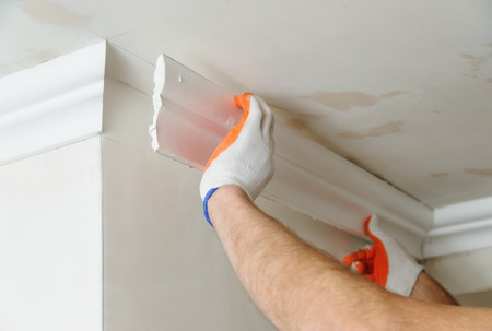 Installation of ceiling moldings. Worker fixes the plastic molding to the ceiling. Фото со стока - 66959997
