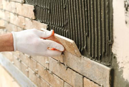 壁のタイルを取付けます。レンガ状のタイルを置く労働者。