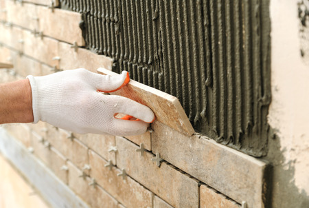 Installing the tiles on the wall. A worker putting tiles in the form of brick.