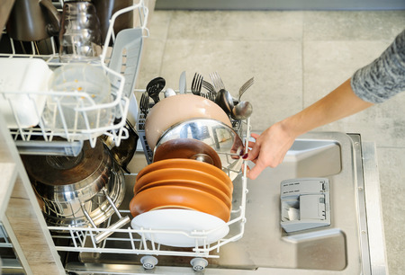 The woman pushed the dirty dishes in the dishwashing machine. Stock Photo