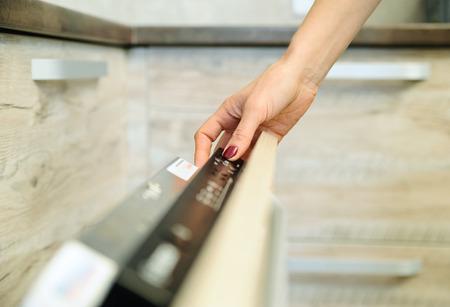 lavar platos: Ejecutar la máquina lavavajillas. El dedo de la mujer que pulsa el botón de inicio.