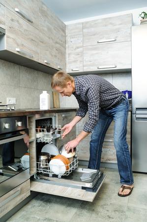 lavar platos: El hombre empujó a los platos sucios en el lavavajillas. Foto de archivo