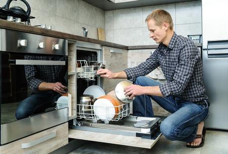 男は、食器洗い機で汚れた皿をプッシュしました。 写真素材
