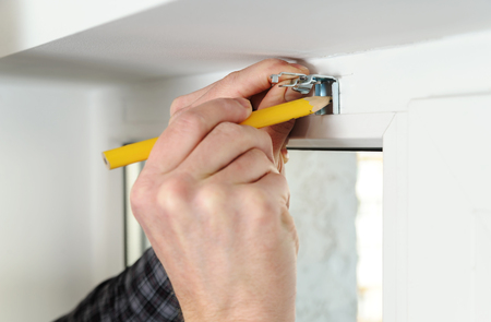 louver: Installing wooden blinds. Man marks the place of mounting jalousie on the windows.