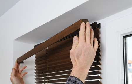 Installing wooden blinds. A man attaches a decorative bar on top. Stockfoto