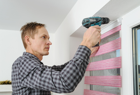 jalousie: Installing fabric roller blinds. The man drilling holes to fix basis rollet.