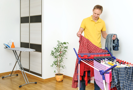The man takes off things from drying rack clothes. Stock Photo