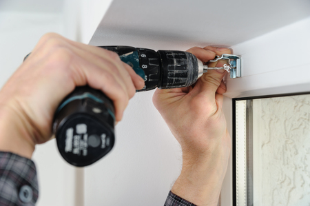 louver: Installing wooden blinds. A man drill hole for fastening metal bracket that holds the jalousie.