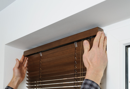 Installing wooden blinds. A man attaches a decorative bar on top. Banque d'images