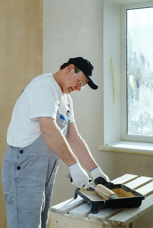 gaining: Painter is gaining paint on the roller dipping into the tray. Stock Photo