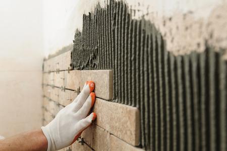 Installation des tuiles sur le mur. Un travailleur de mettre des tuiles sous la forme de briques. Banque d'images - 73203062