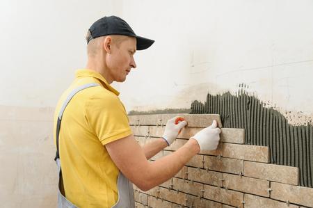 壁のタイルを取付けます。労働者はレンガ状のタイルを置きます。