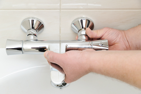 Installing Faucet With Thermostat. Man\'s Hands Are Fixing Bath ...